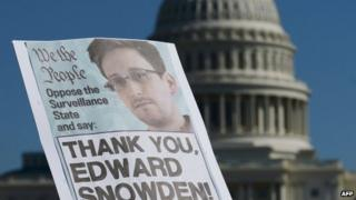 In this file photo dated 26 October 2013 shows demonstrators hold placards supporting former US intelligence analyst Edward Snowden during a protest against government surveillance in Washington DC