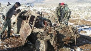 Lebanese soldiers inspect a car damaged by the bombing in the Bekaa Valley in 17 December 2013