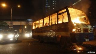 A bus burns on a street in Dhaka (October 2013)