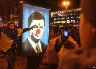 A defaced photo of Ukrainian President Viktor Yanukovych in Kiev, 19 December