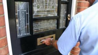 Postman putting letters through a letter box