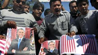 Activists of Sanskriti Bachao Manch, or save culture forum, burn posters of U.S. President Barack Obama and U.S. flags during a demonstration to protest against the alleged mistreatment of New York based Indian diplomat Devyani Khobragade, in Bhopal, India, Wednesday, Dec. 18, 2013.