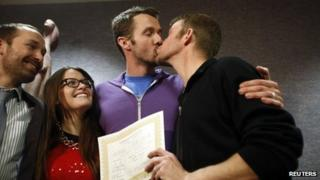The first gay couple to be married in Utah, Michael Ferguson (2nd R) and his husband Seth Anderson (R), kiss as Blake Ferguson (L) and his girlfriend Danielle Morgan watch after the pair married at the Salt Lake County Clerks office in Salt Lake City, 20 December 2013
