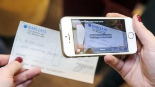 woman photographs cheque