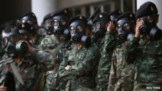Soldiers wear gas masks as they stand guard at the Thai-Japan youth stadium in central Bangkok, 26 December 2013