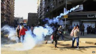 Demonstrator throws tear gas towards security forces in Cairo (27/12/13)