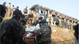 Indian rescuers use a stretcher to carry a body near a charred carriage.