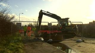 Workman at the road affected by a burst pipe