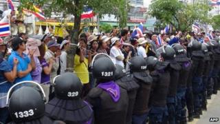 Thai protesters rally along a line of riot police, Bangkok (28 December)