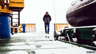 Crew-member of Akademik Shokalskiy walk on snow-covered deck