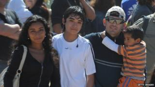 Chilean miner Alex Vega (right, holding a boy) arrives at the San Jose mine for a mass near Copiapo on 17 October, 2010