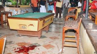 "Members of the public view some blood stains on the floor next to a pool table at the Tanduri Bar and Night Club in Ukunda which is 40km south of Kenya""s coastal town of Mombasa.,"