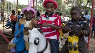 Kenyan children with painted faces enjoy a ride on a toy horse during New Year's celebrations at Uhuru Park in Nairobi, Kenya, Wednesday, 1 January 2014