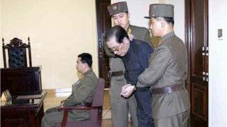 Jang Song Thaek, with his hands tied with a rope, is dragged into the court by uniformed personnel in this December 13, 2013 picture taken from Rodong Sinmun December 12, 2013