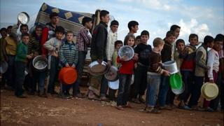 Displaced Syrian children line up for food distribution in the Maiber al-Salam refugee camp