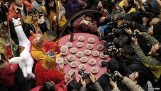 People take pictures of three men (left, from top to bottom) dressed as Zhu Bajie, Tang Dynasty Buddhist monk Xuanzang and Monkey King Sun Wukong, who are all characters from the Chinese classic novel Journey to the West, as they eat laba porridge during the Laba Festival at the Xuanzang Temple in Nanjing, Jiangsu province, 8 January 2014