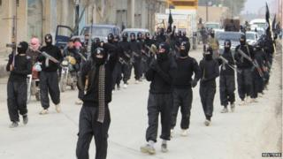 Fighters of al-Qaeda linked Islamic State of Iraq and the Levant carry their weapons during a parade at the Syrian town of Tel Abyad, near the border with Turkey (2 January 2014)