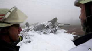 Firefighters stand next to the charred wreckage of the plane near Trier, western Germany, 12 January