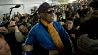 Former NBA basketball player Dennis Rodman is followed by journalists as he arrives at the Capital International Airport in Beijing from Pyongyang, Monday, 13 January 2014