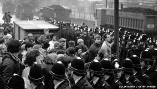 Striking miners watch coal leaving their pit under police guard
