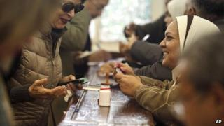 An election worker checks the identification of a woman at a polling site in Cairo