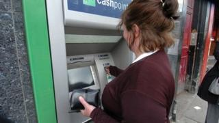 Woman removing money from ATM