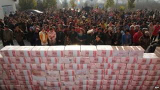 "This picture taken on January 14, 2014 shows villagers waiting before a two-metre-long ""money wall"" built with cash for their year-end bonus at Jianshe village of Lianshan municipality, southwest China""s Sichuan province"