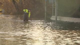 A workman knee deep in flood water