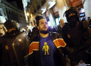 Riot police detain a Burgos solidarity protester in Madrid, 16 January