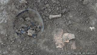 Surface of grave, with pottery, skull and finger bone