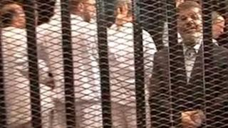 The ousted president of Egypt (in dark jacket), Mohammed Morsi, in court for a hearing, 4 November 2013