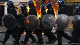 LONDON, ENGLAND - AUGUST 08: Riot police walk along Clarence Road in Hackney on August 8, 2011 in London, England