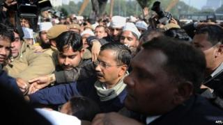 New Delhi Chief Minister Arvind Kejriwal (C) is surrounded by policemen and people protecting him as he makes his way through a crowd of supporters and media during a protest in the streets of New Delhi on January 20, 2014