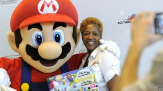 A woman stood with Super Mario and a Nintendo console