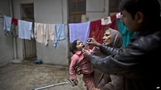 A Pakistani health worker, right, gives a polio vaccine to a child held by her grandmother at their home in Rawalpindi, Pakistan, Monday, Jan. 20, 2014.