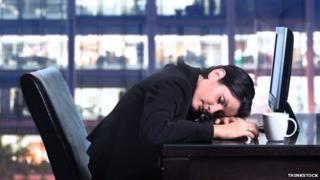 Woman at desk asleep at night