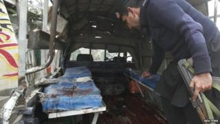 A policeman collects evidence from a police mobile van after it was hit by a bomb blast in Charsadda, on the outskirts of Peshawar January 22, 2014.