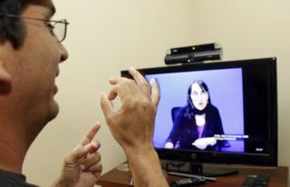A man talking to a remote interpreter via video relay