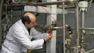 An unidentified International Atomic Energy Agency (IAEA) inspector cuts the connections between the twin cascades for 20 percent uranium enrichment at the Natanz facility (20 Jan. 2014)