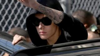 Justin Bieber raises a fist as he exits a Miami jail on January 23, 2014.