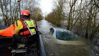 Members of the Avon and Somerset Police Underwater Search Unit inspect a submerged abandoned car as they head to the village of Muchelney in Somerset