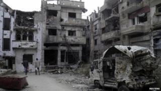 Man walk through damaged buildings in the besieged area of Homs