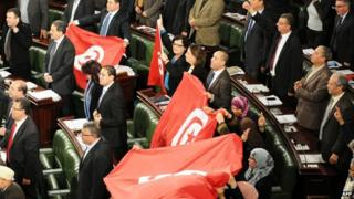 Members of the Tunisian National Constituent Assembly (NCA) wave flags to celebrate the adoption of a new constitution on 26 January 2014, in Tunis.