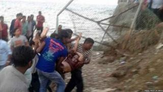 Rescuers carry a victim after a tourist boat capsized in the Bay of Bengal in the Andaman and Nicobar Islands.