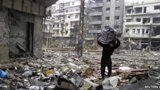 A man carries a bag amid damage and debris in the besieged area of Homs