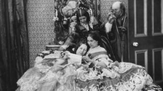 A Victorian family gathered together reading a letter