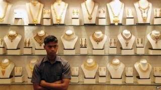 An Indian salesman stands by a counter at a gold jewelery shop in Mumbai