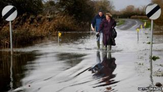 Two people wade through flood waters at Burrow Bridge