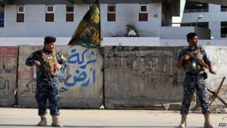 Iraqi policemen stand guard outside a building occupied by a state-owned company that was stormed by attackers in the northeast of the capital Baghdad (30 January 2014)
