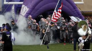Northwestern University football players take the field in a game on November 16, 2013